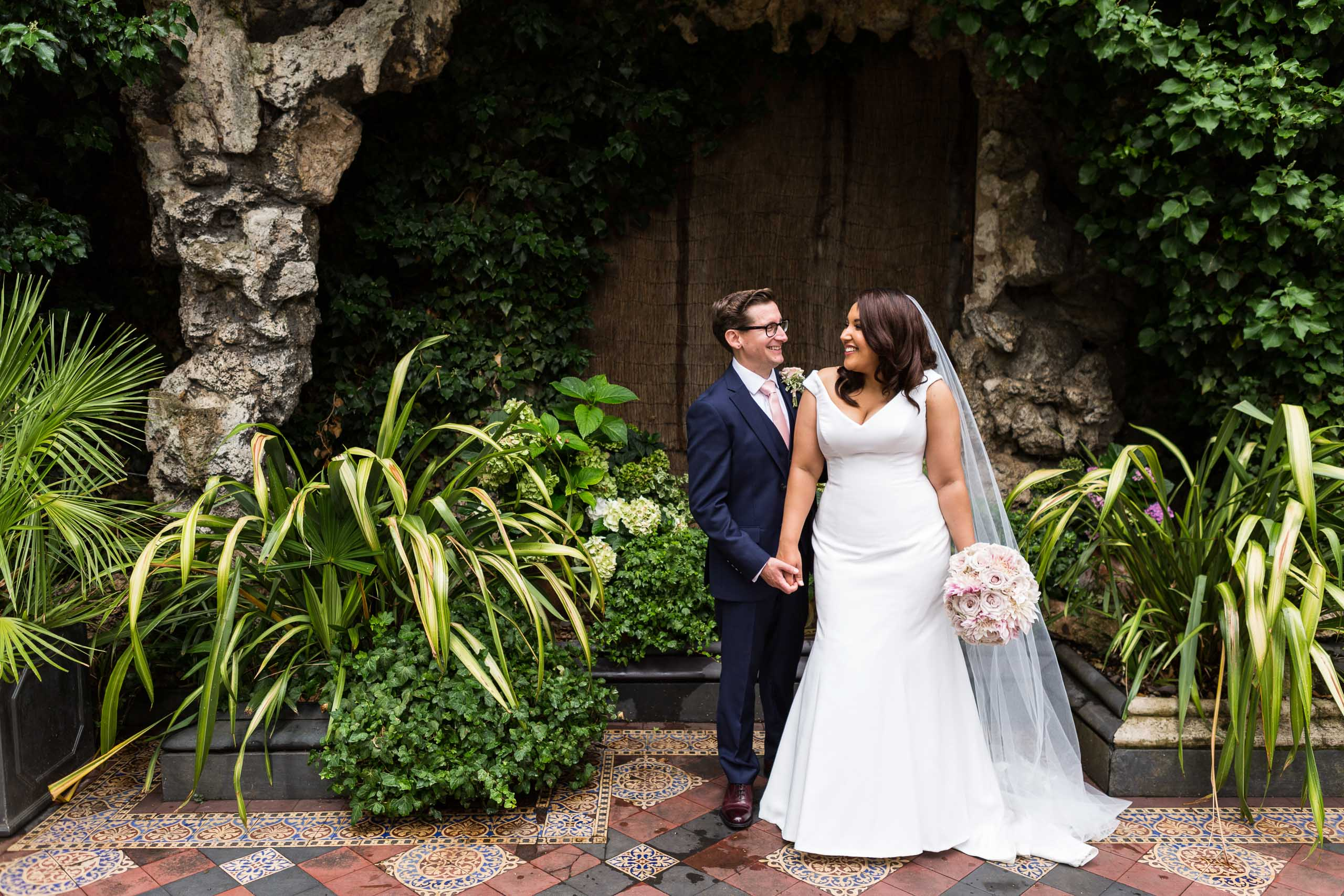 A newlywed couple smile at each other in a garden on their wedding day