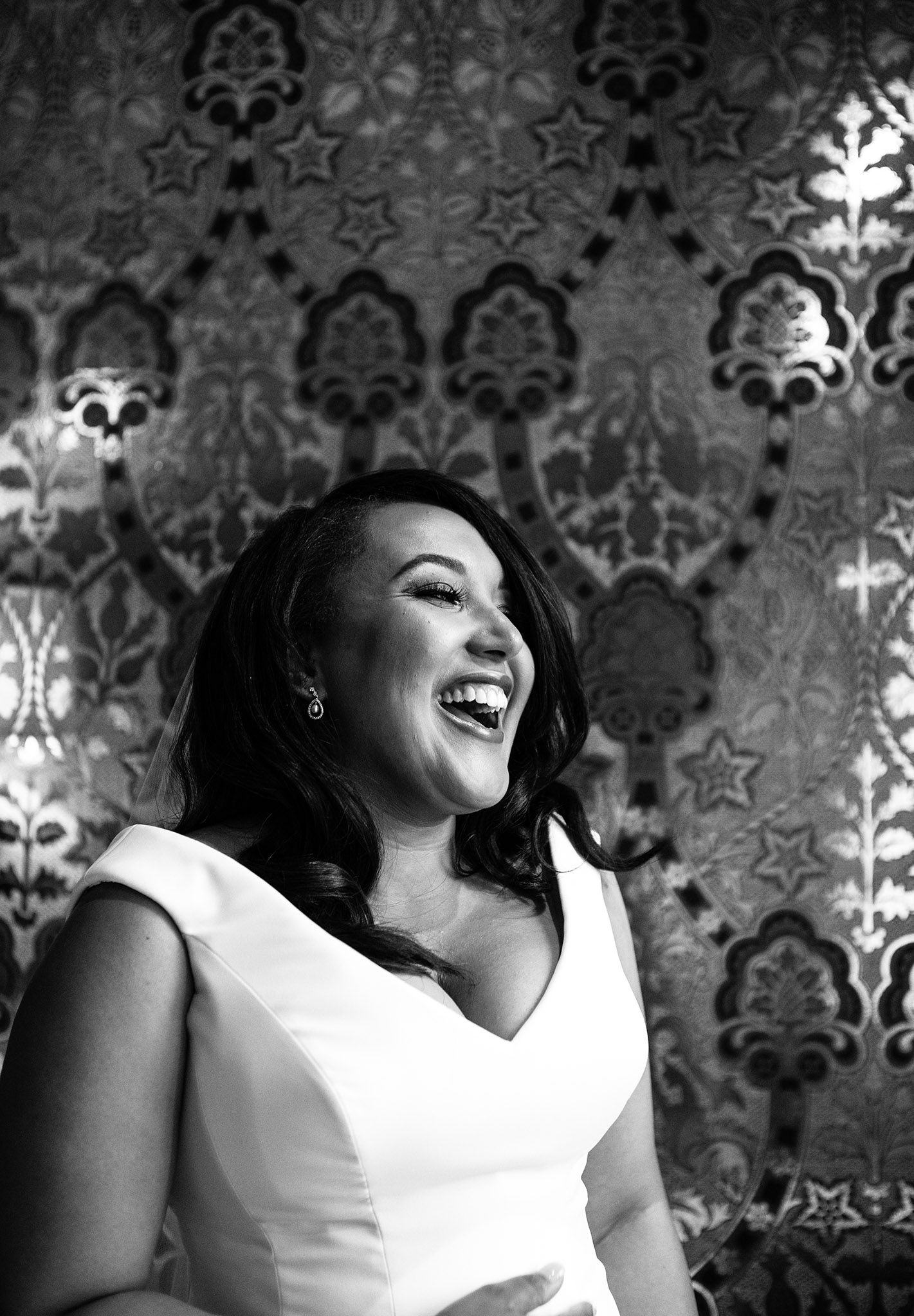 A black & white photo of a bride laughing with patterned wallpaper in the background