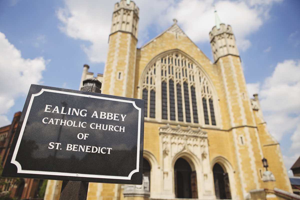 A wide shot of Ealing Abbey with a black sign in the foreground saying Ealing Abbey Catholic Church