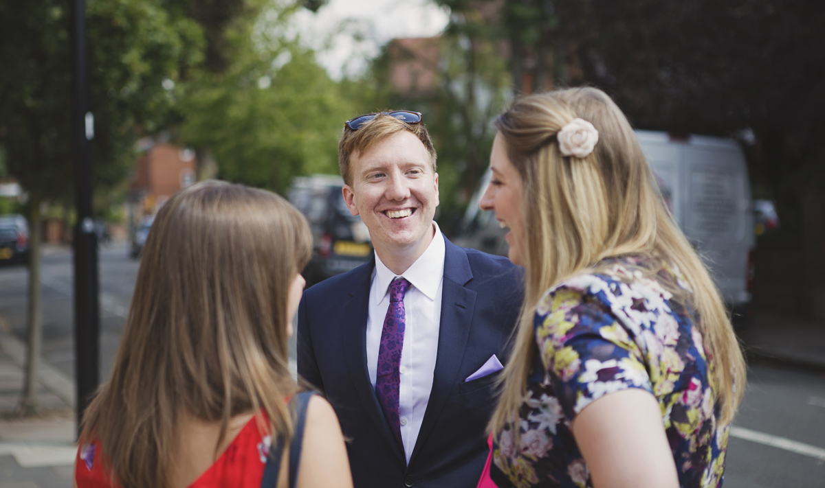 A man smiling at guests at a wedding