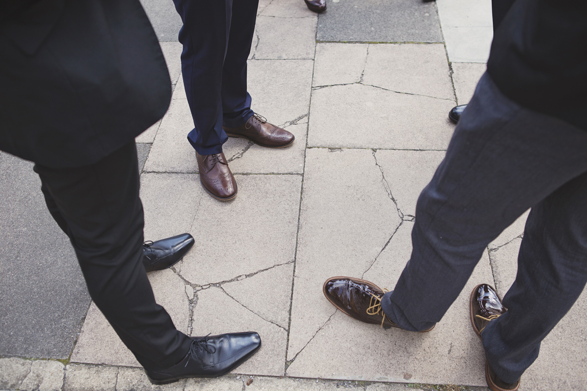 A shot of three mens' formal shoes as they stand on a pavement