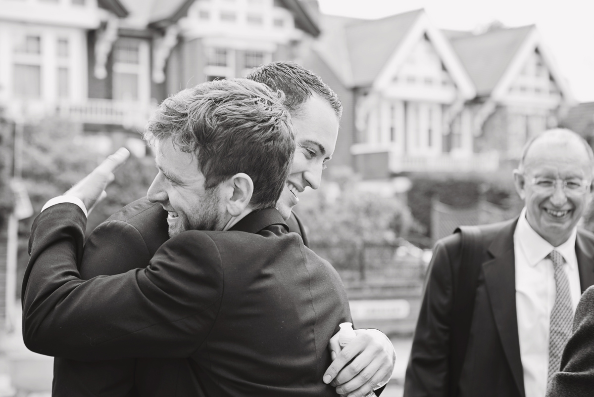A black and white shot of two men hugging at a wedding