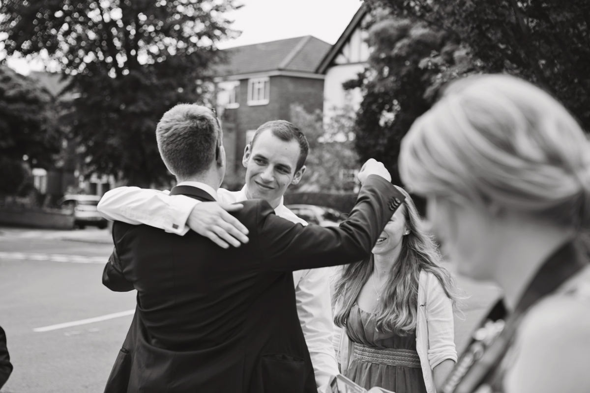 A black and white shot of two men about to hug with wedding guests