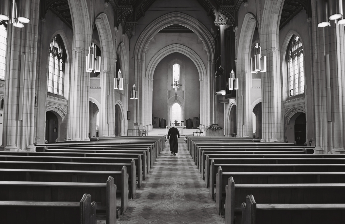 A black and white photo of a priest walking to the alter in an empty church