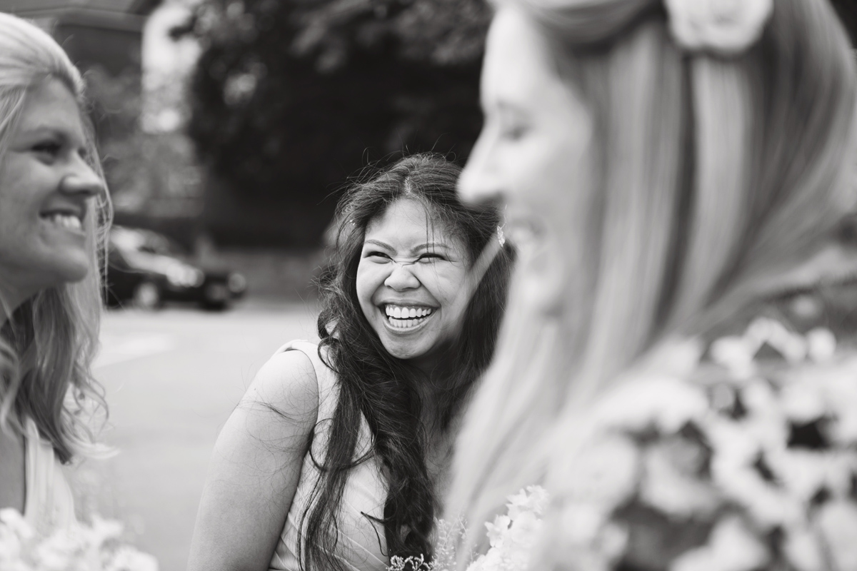 A mono image of a bridesmaid laughing at a wedding