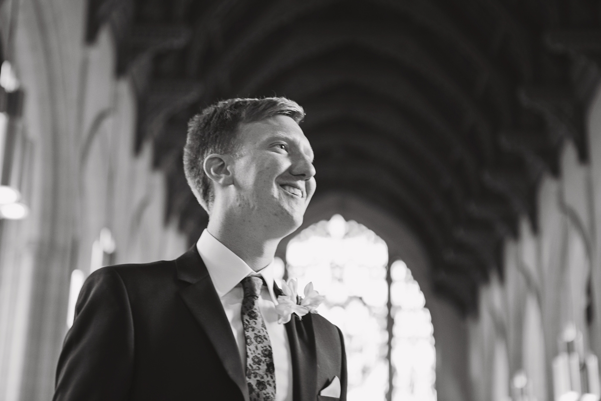 A mono shot of a groom smiling in a church