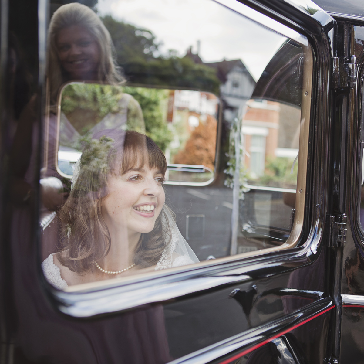 A smiling Bride looking out of the window of a black taxi