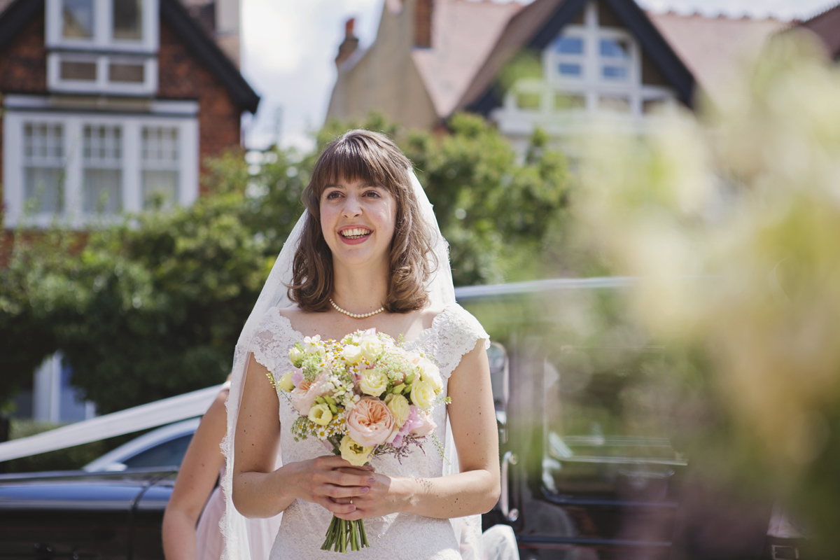 A bride clutching her bouquet and smiling in the sunshine