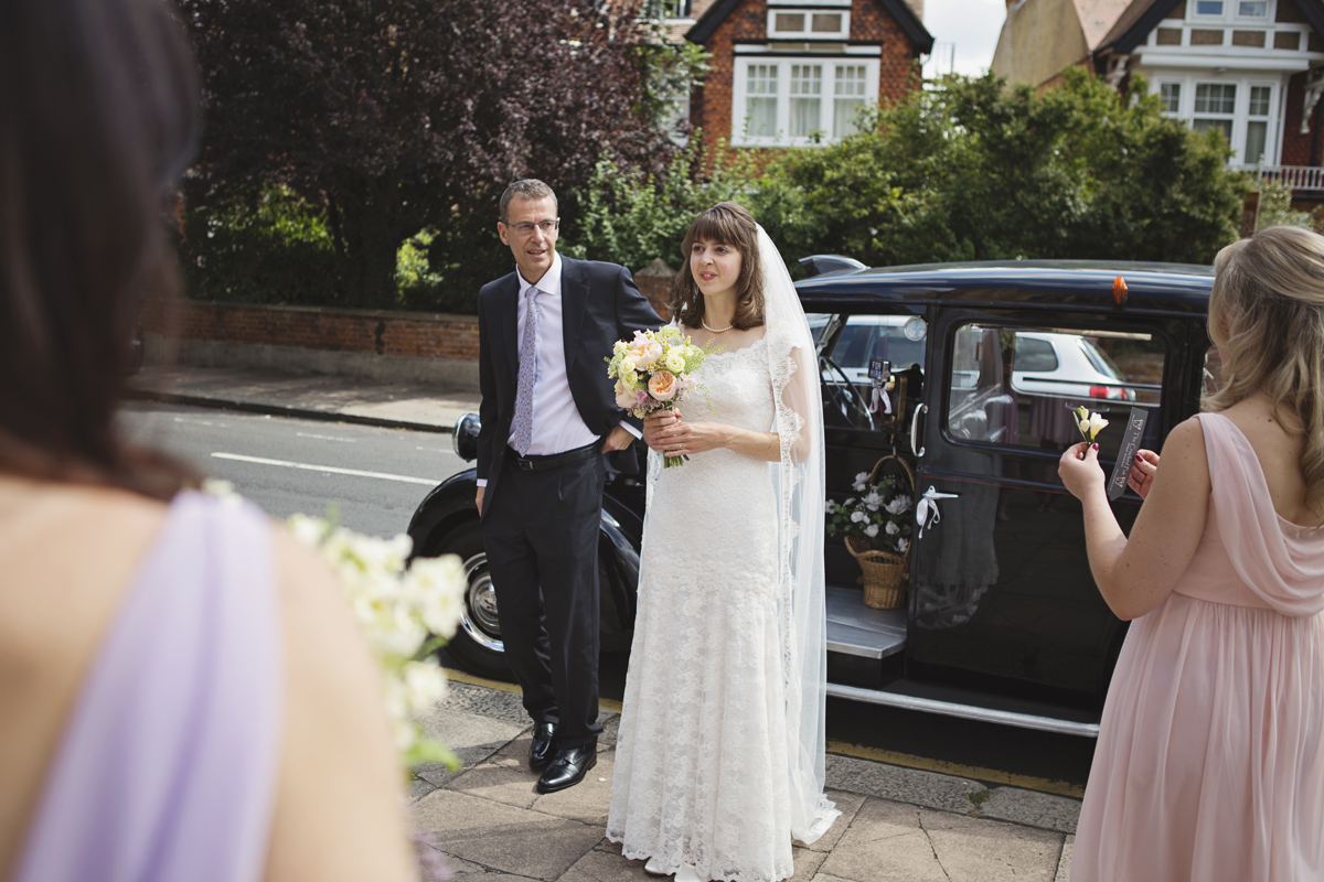 A Bride and her father standing in front of a taxi at a wedding
