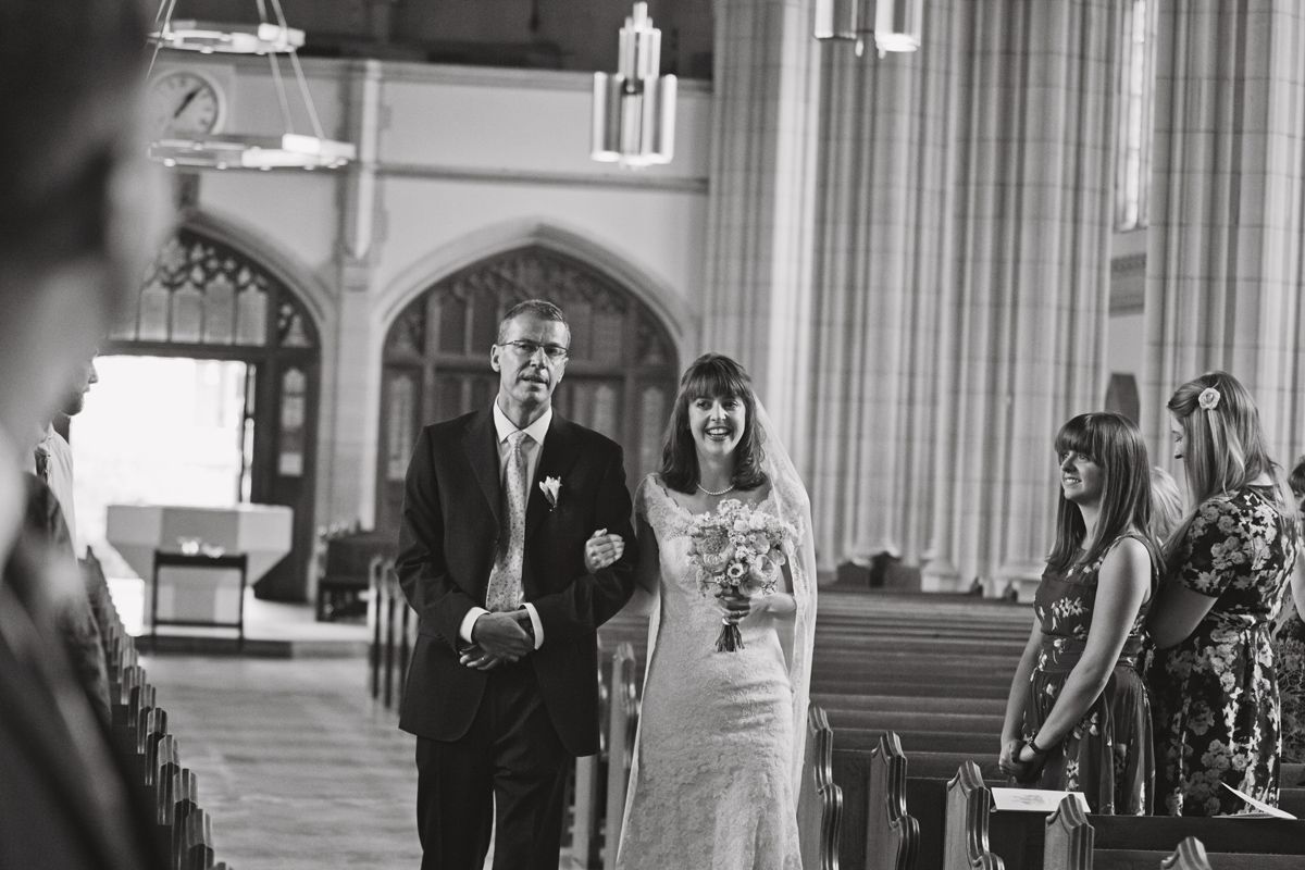 A black and white shot of a bride and her father walking down the aisle