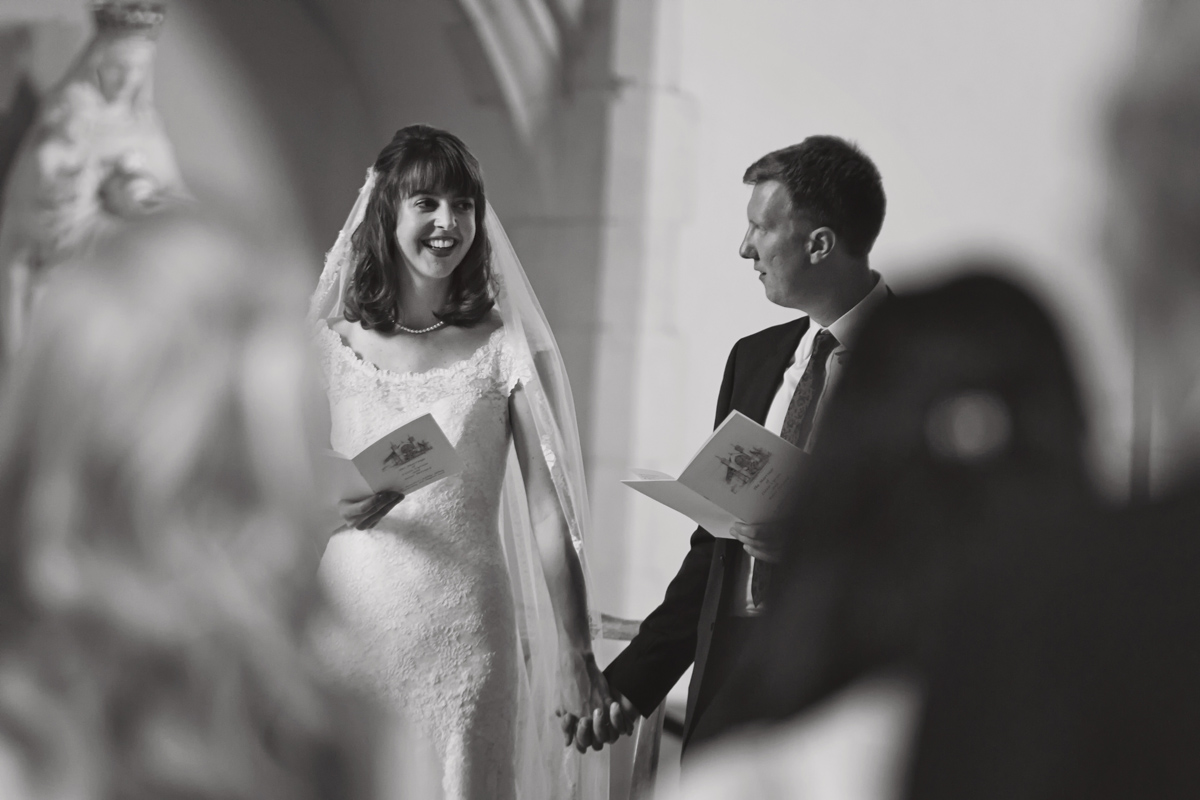 A mono shot of a bride and groom in church smiling
