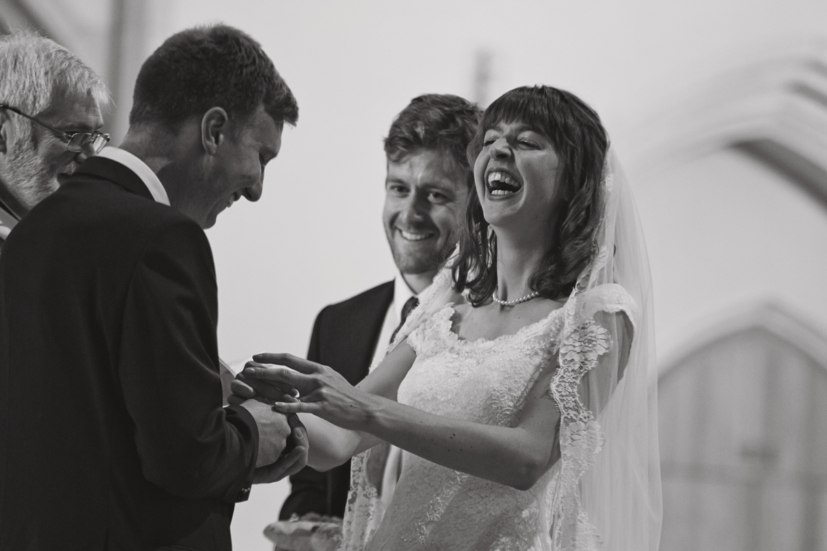 A black and white picture of the bride laughing as she receives her ring at a wedding