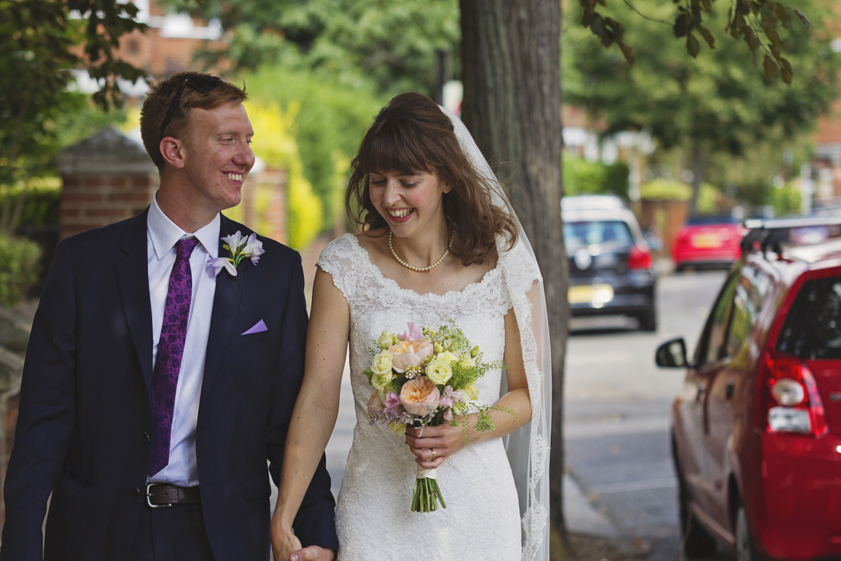 Newlyweds walking down a street laughing