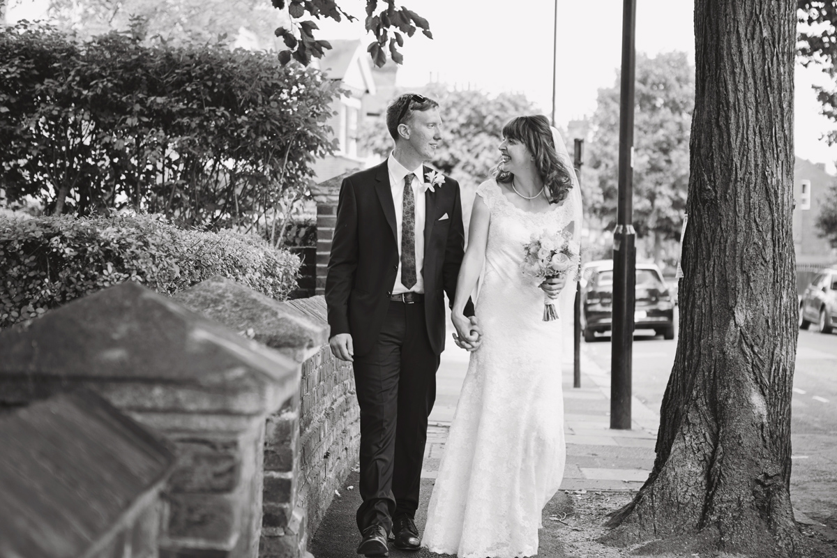 A mono image of a bride and groom walking down the street smiling