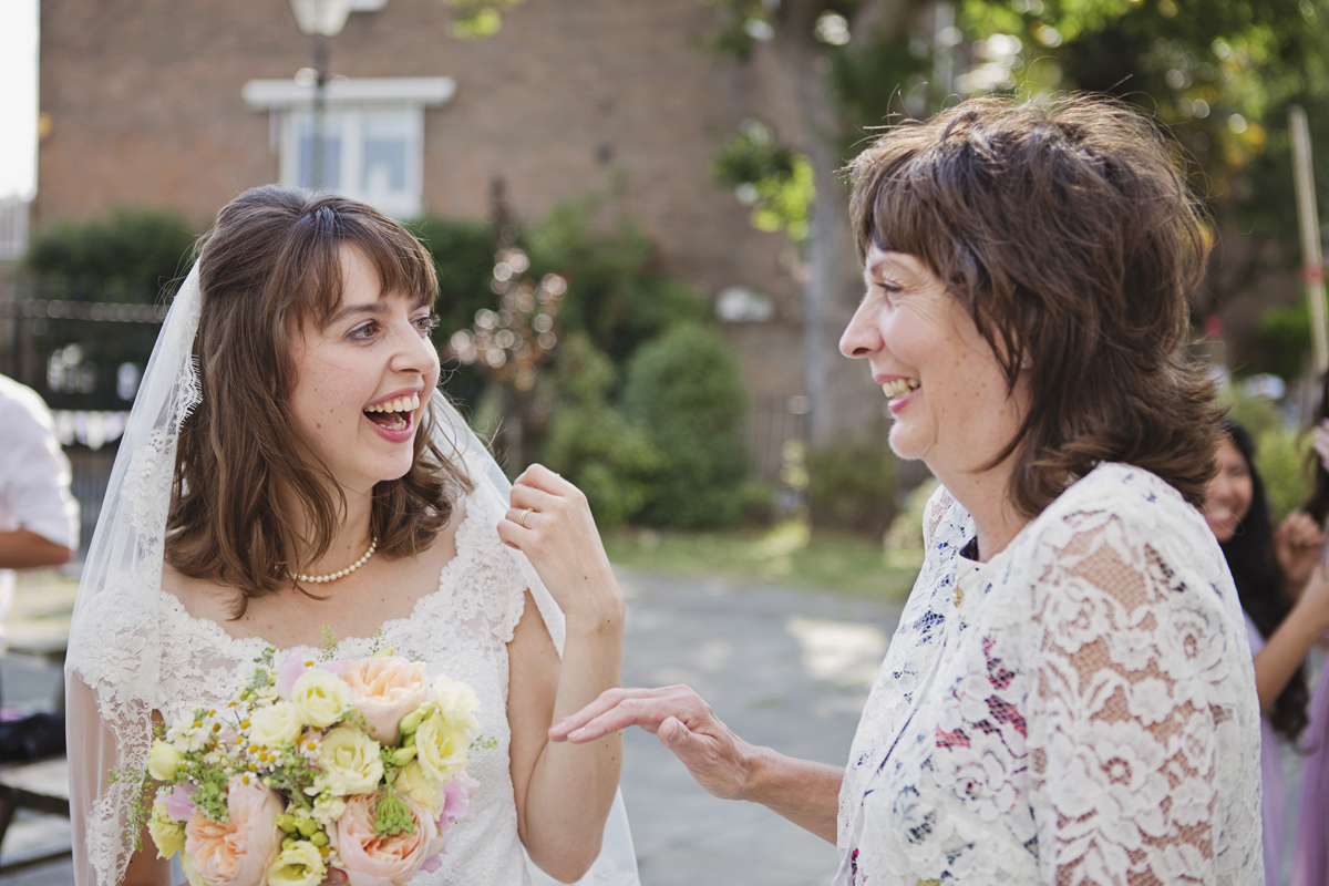 A bride laughing with her mother at a wedding reception