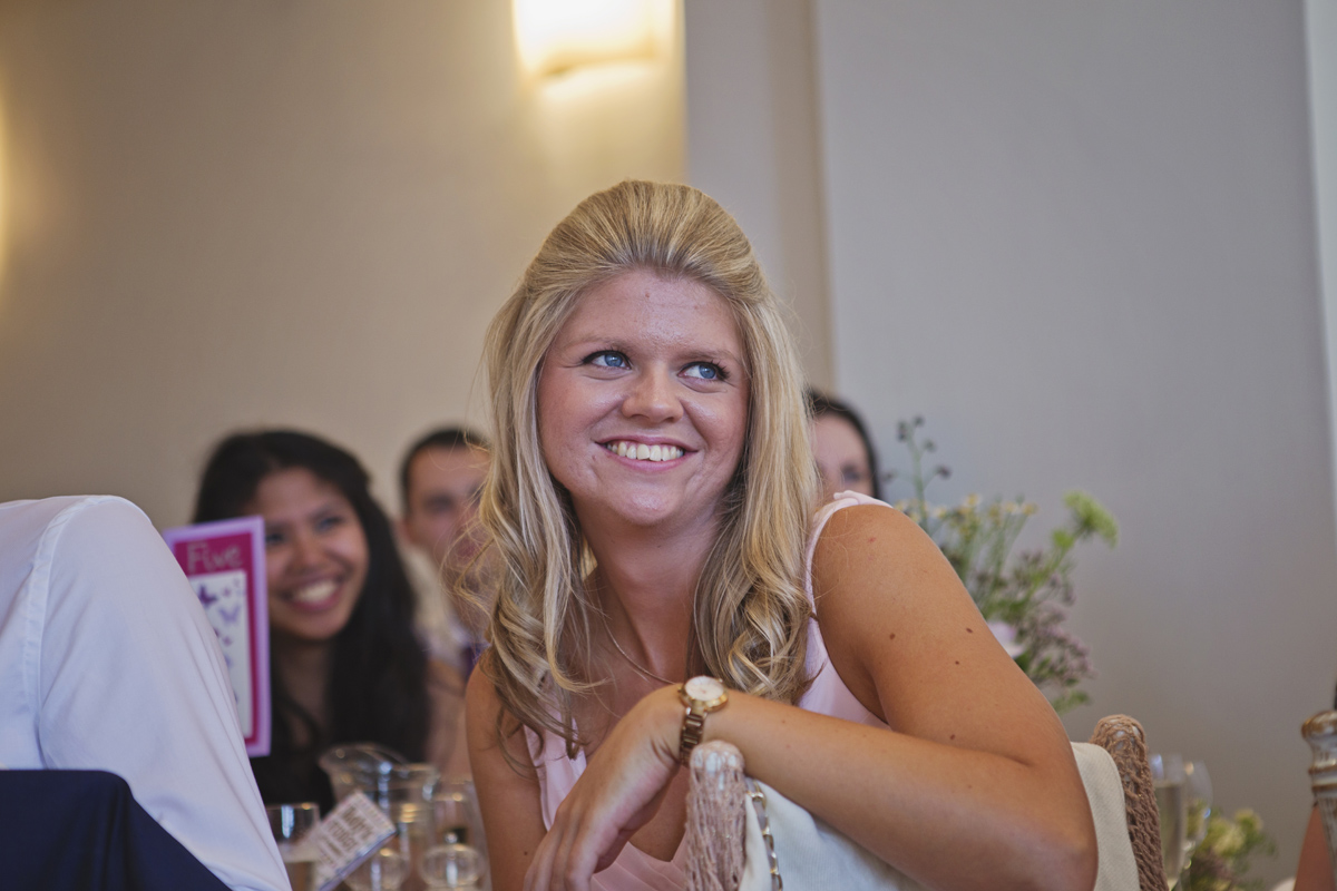 A lady sitting at a wedding reception smiling as she watches the speeches