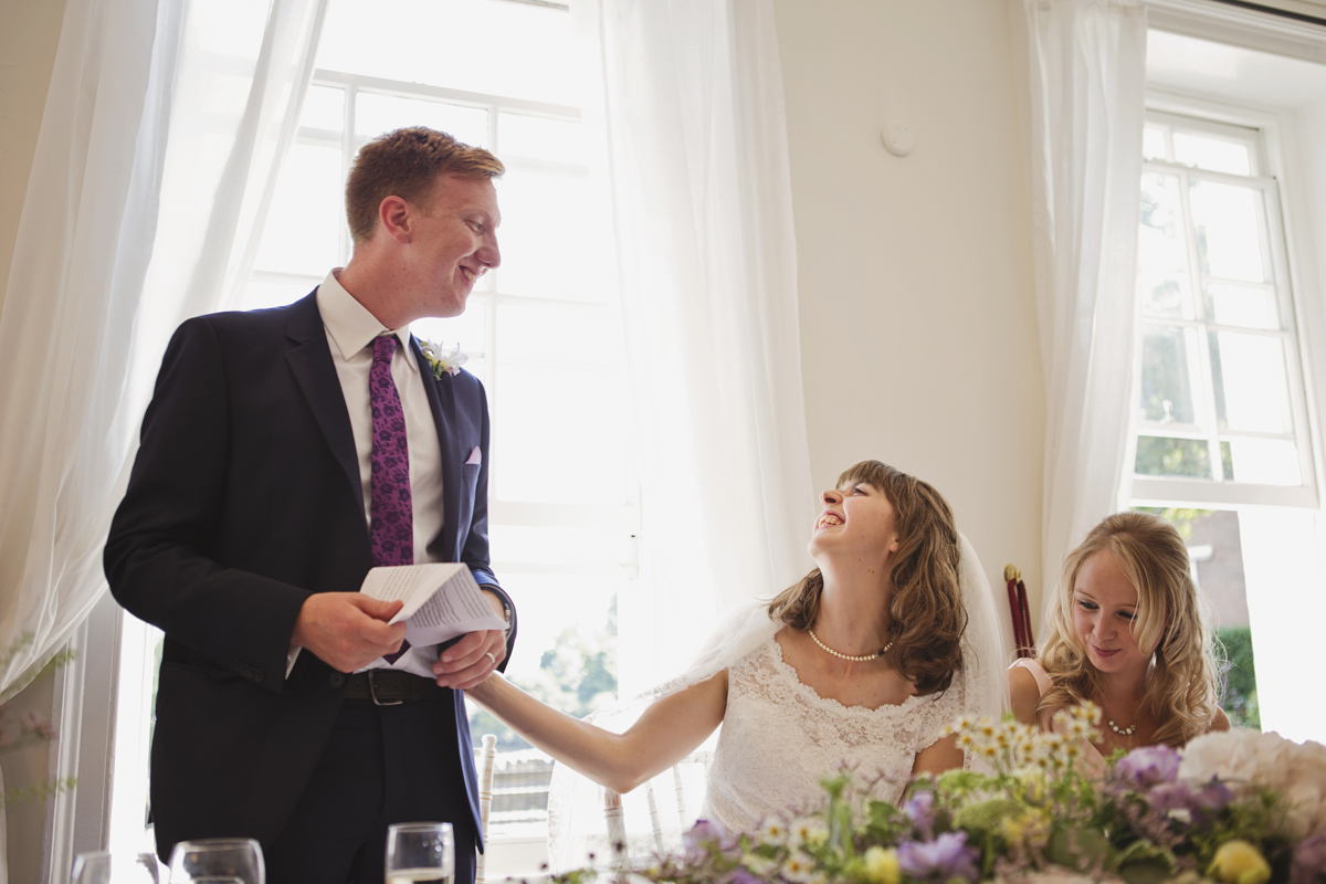 A bride touches her husband's hand as he gives a wedding speech