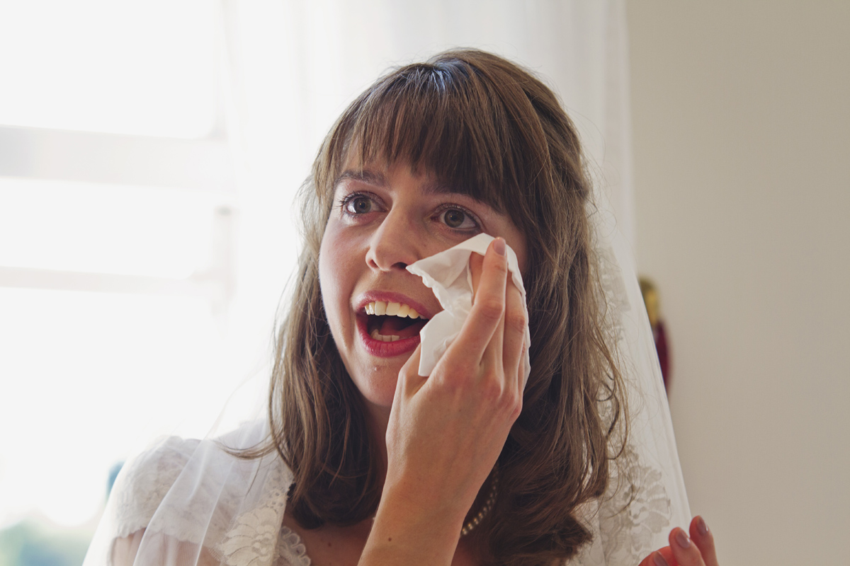 A bride holds a tissue to her eye as she cries during the speeches