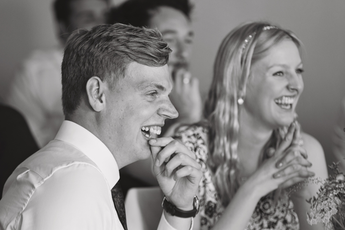 A mono shot of wedding guests laughing