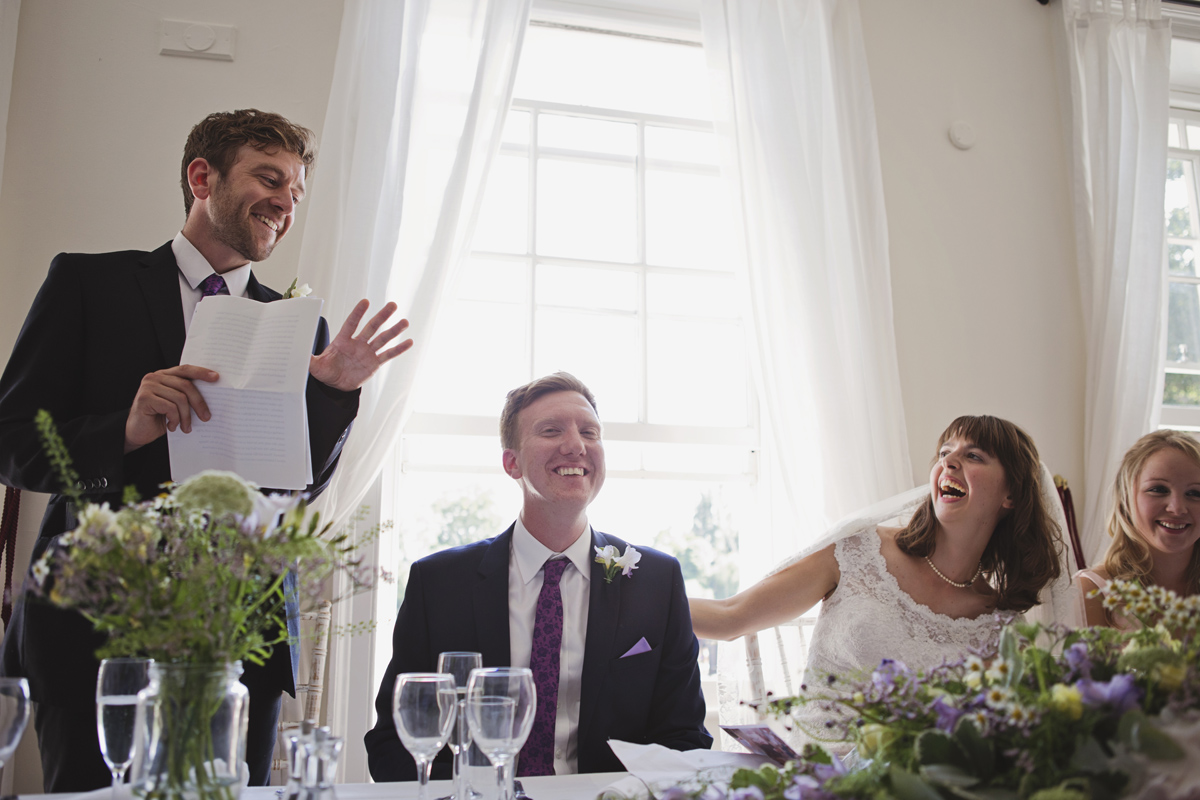 A Best Man gives his speech while the bride and groom laugh at a wedding