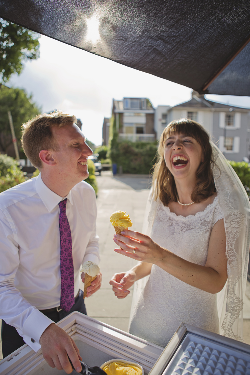 A wedding couple laughing as they eat ice cream at a wedding