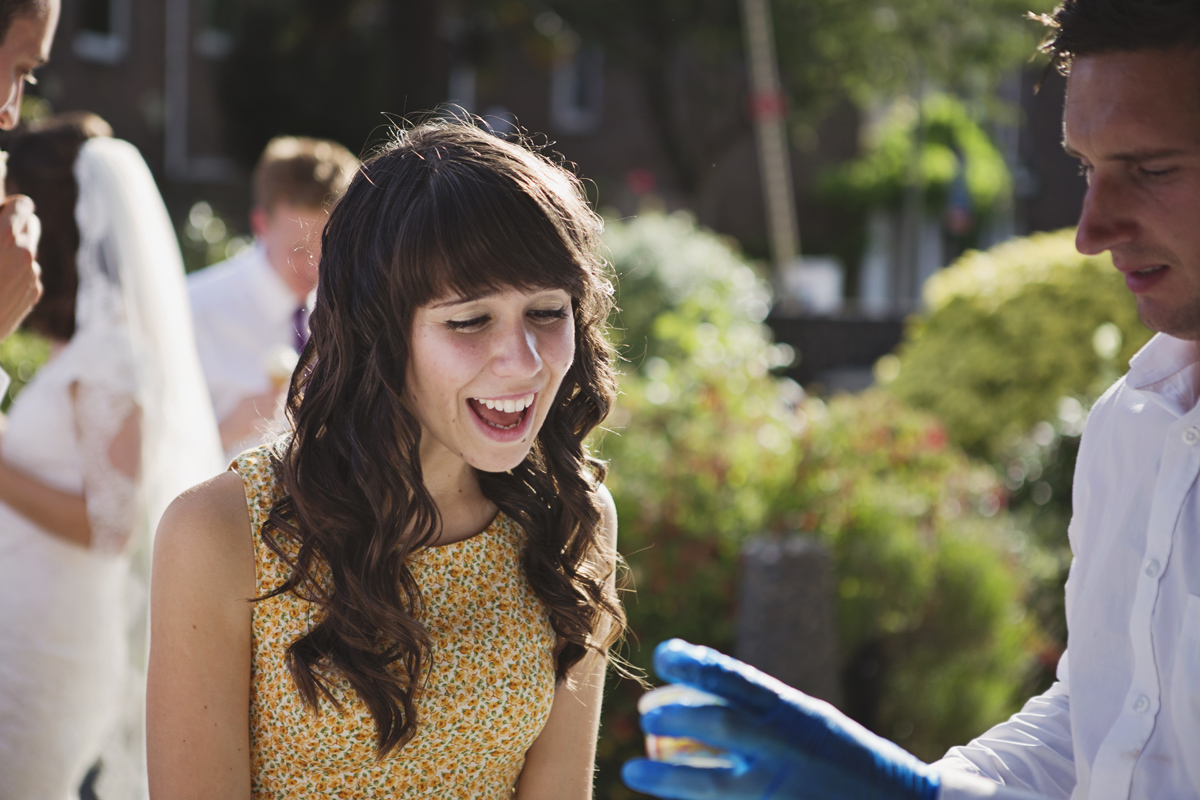 A woman guest laughs at a wedding as she is served ice cream outdoors