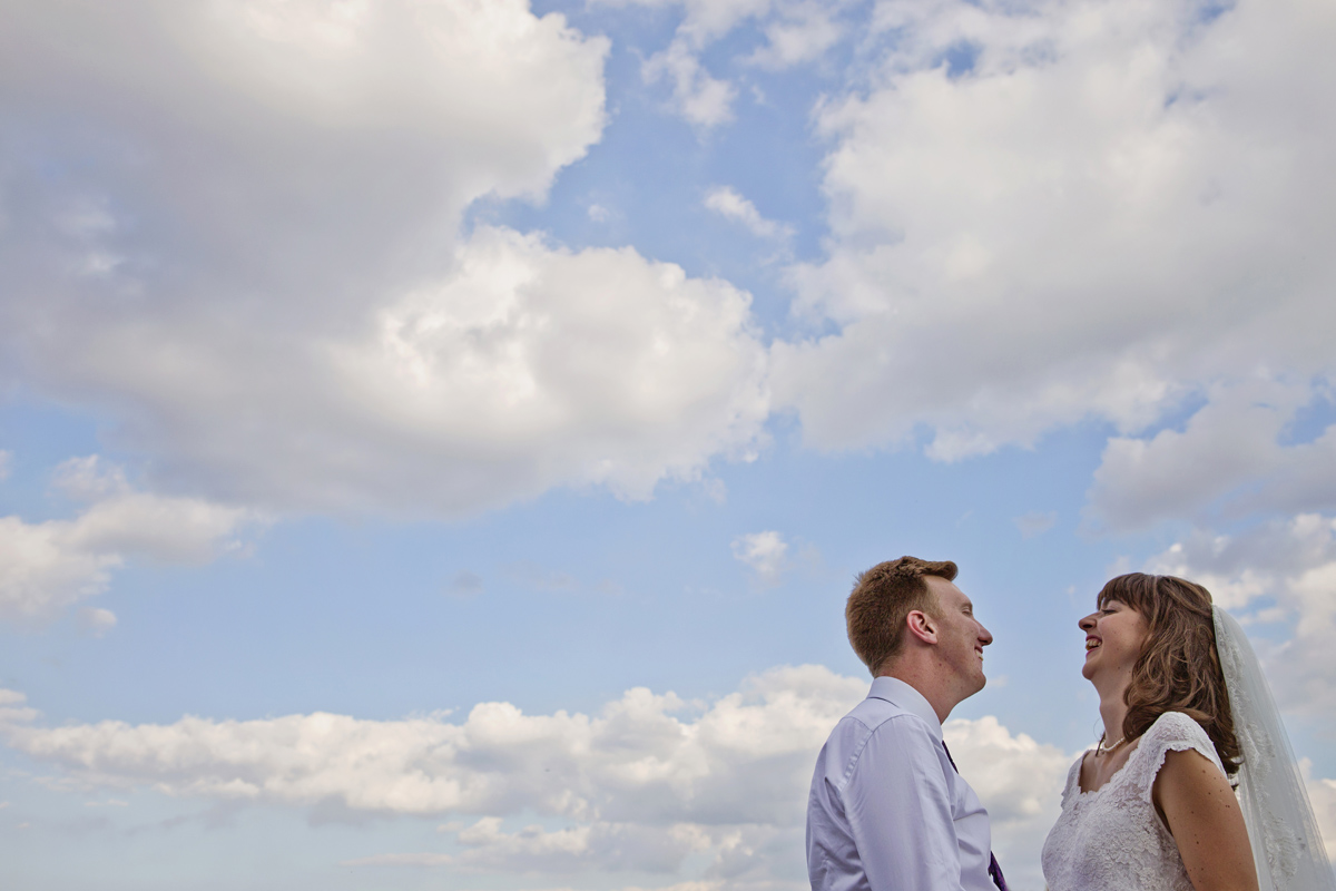 Newlyweds facing each other and laughing with clouds behind them