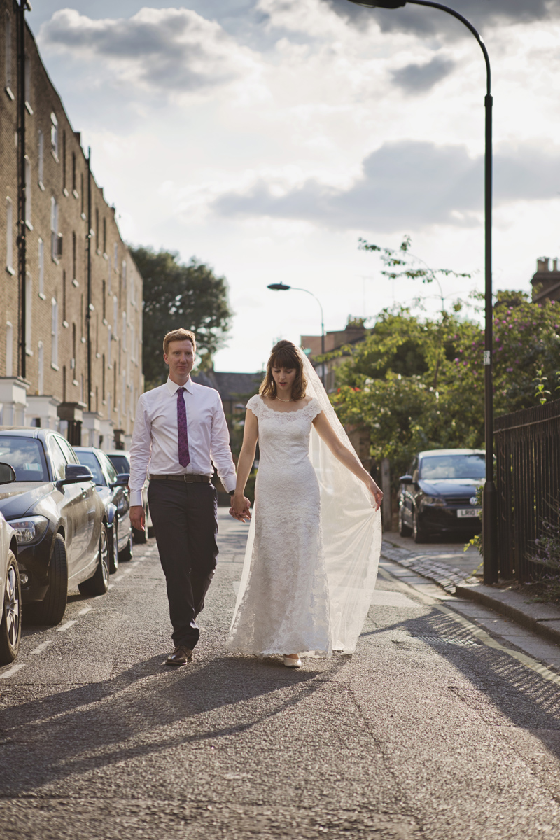 A Bride and Groom walking down a street in the sunshine