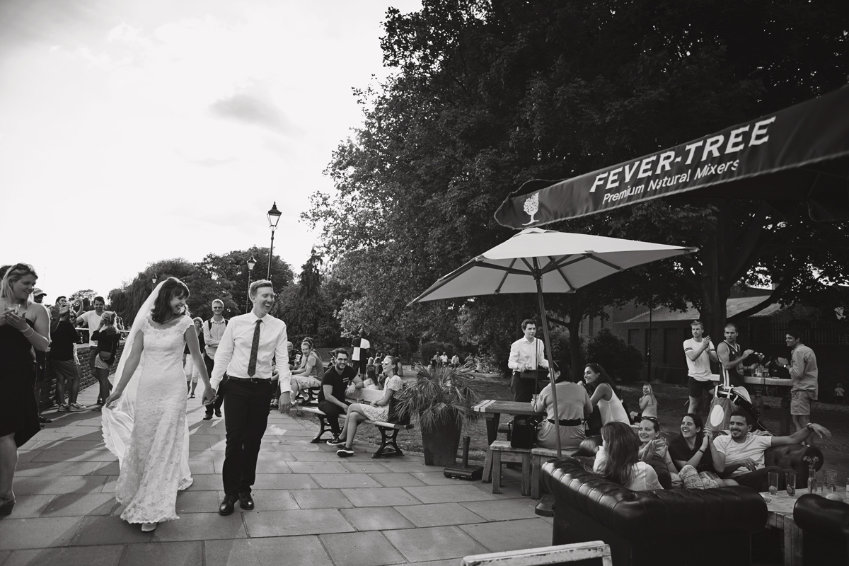 A black and white shot of newlyweds walking past a beer garden with drinkers smiling at them