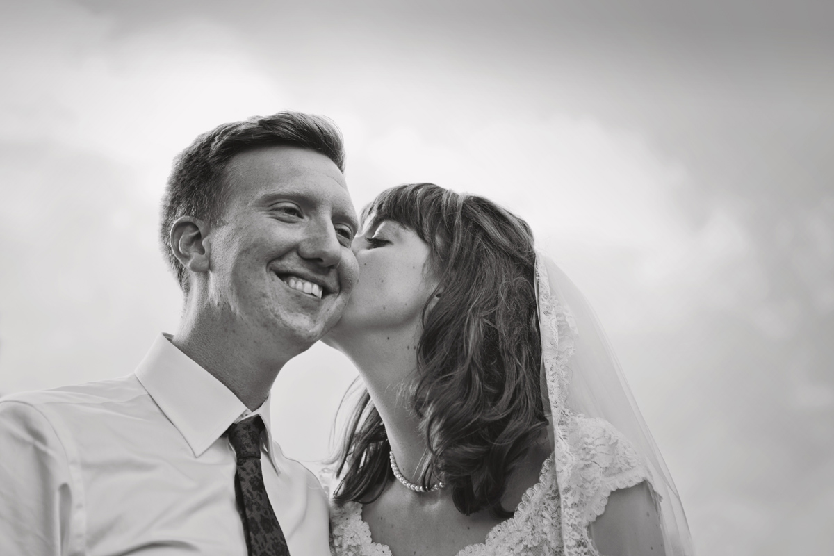 A bride kisses her smiling husband on the cheek in black and white