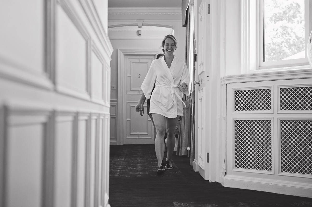 A smiling bride to be walking down a corridor in a towel robe
