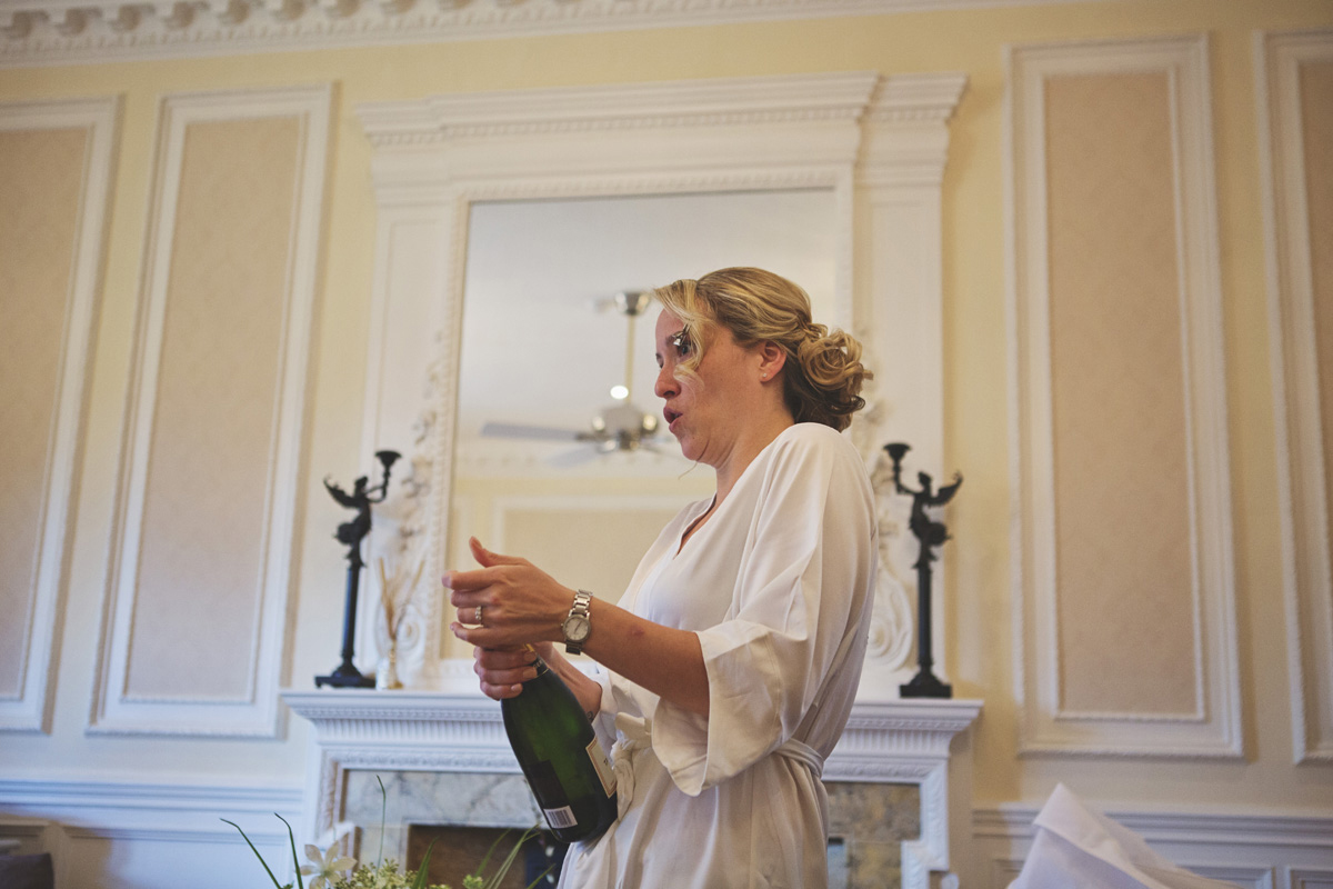 A bride to be popping a cork on a bottle of champagne
