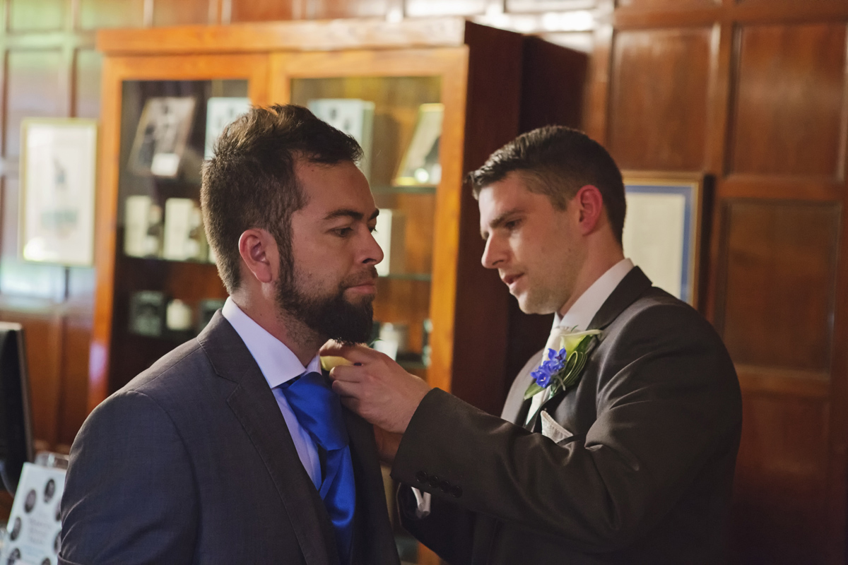 A groom fixes a button hole on his best man