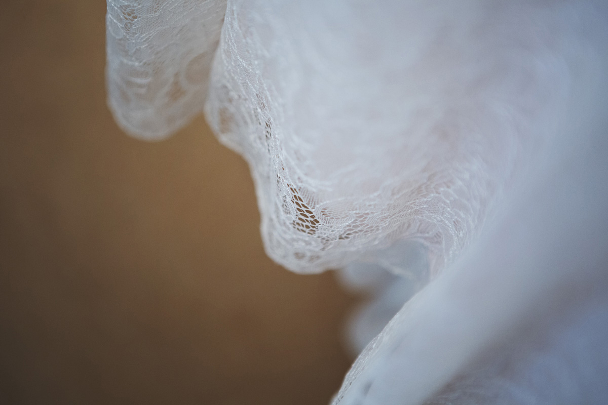 A close up of the lace hem on a wedding dress