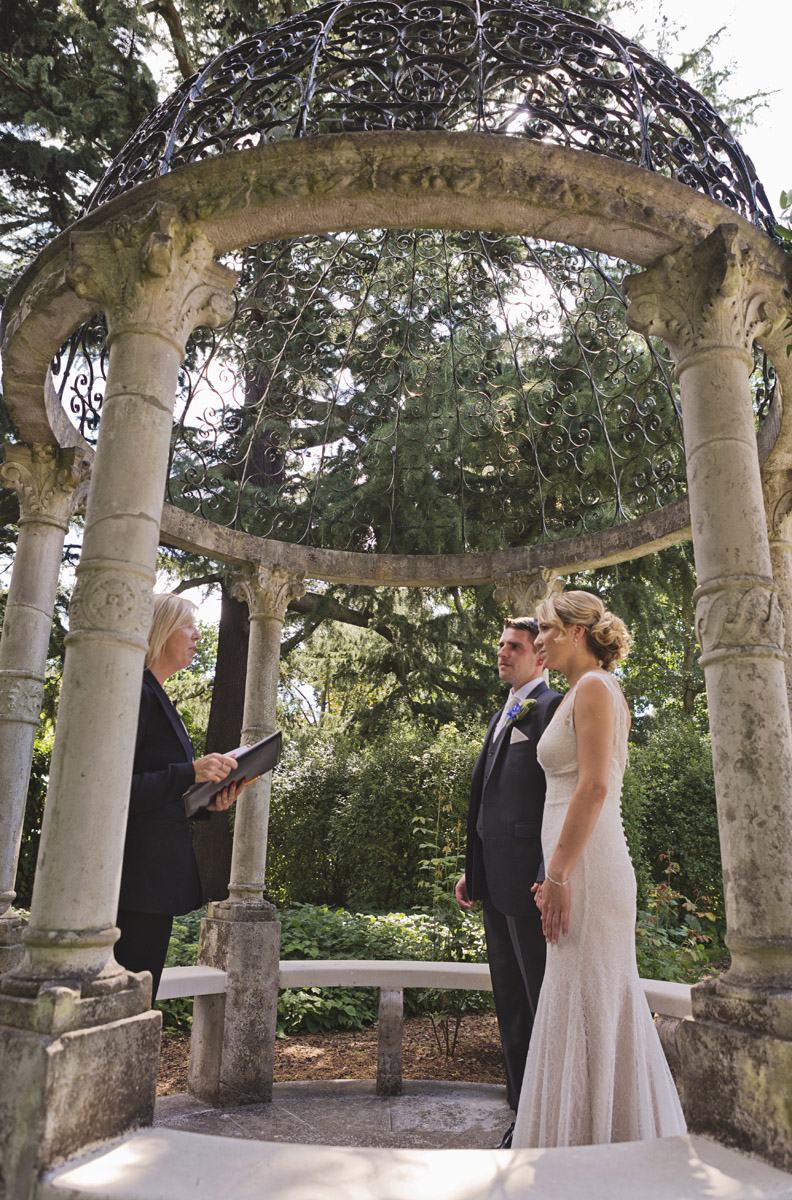 A bride and groom with an officiant standing under a gazebo