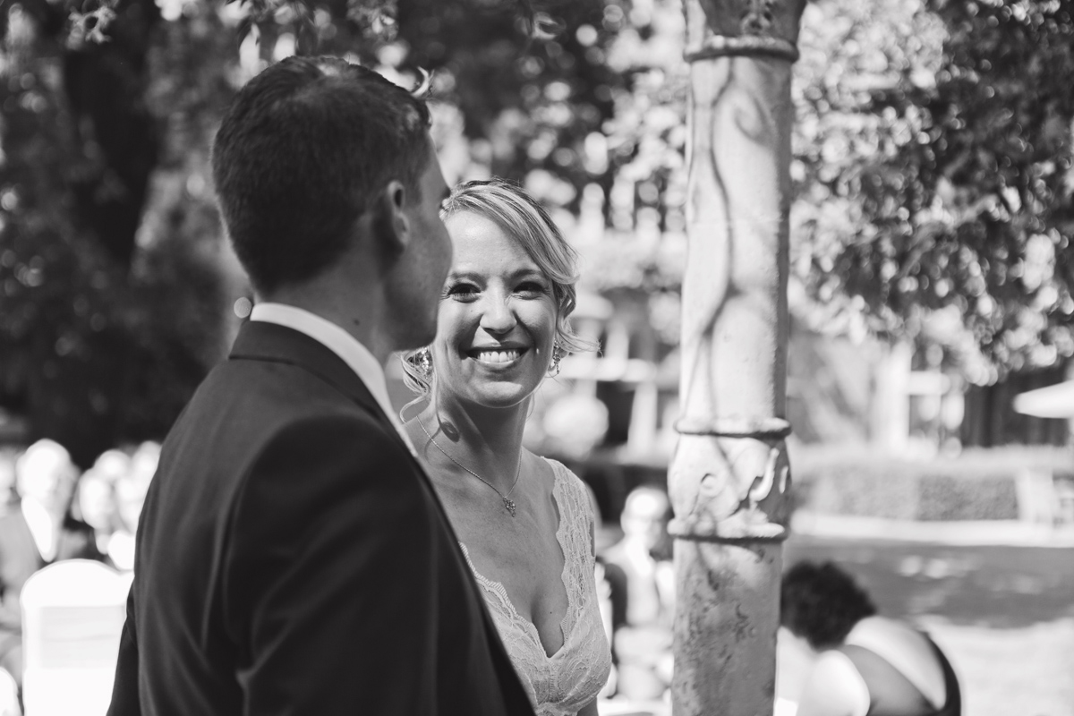 A black and white image of a bride smiling at the groom during their vows