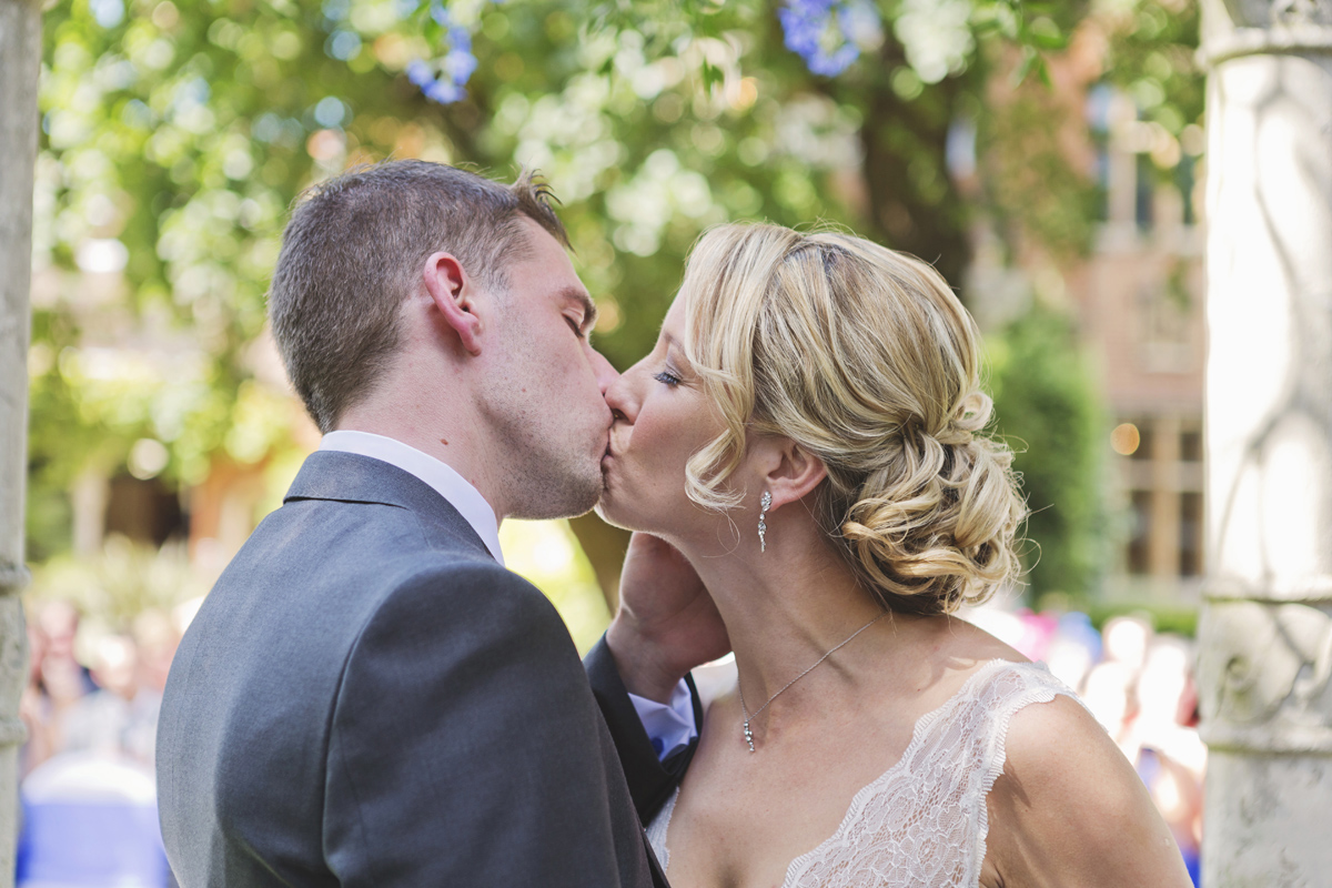A bride and groom kiss after their wedding ceremony