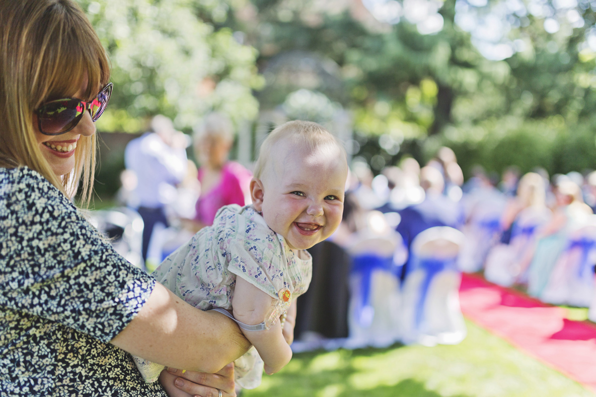 A baby smiles at the camera at a wedding