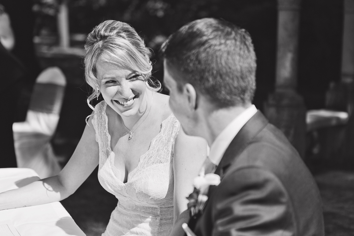 A bride smiles at her husband while signing the register at a wedding
