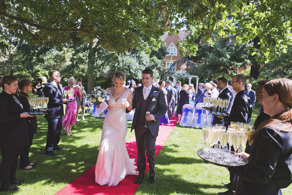 A wedding couple walking down the aisle at a garden wedding in the sunshine