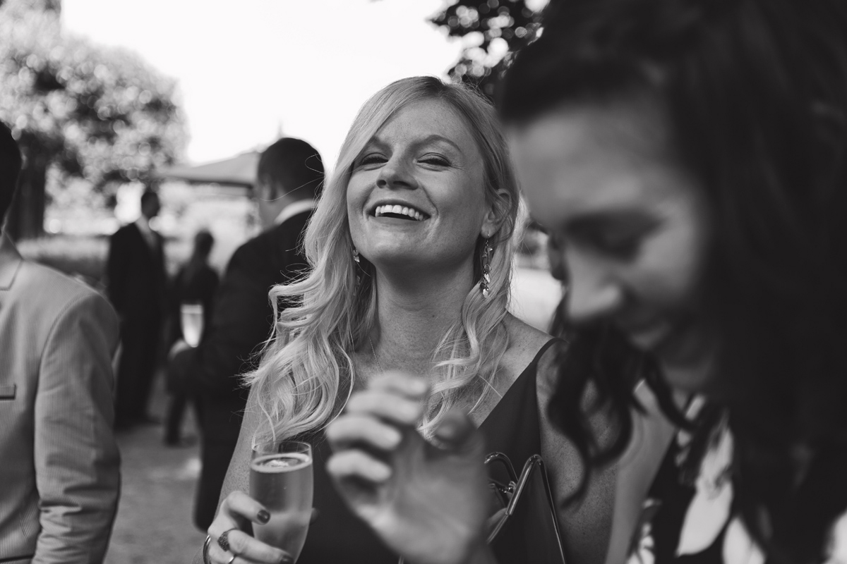 A black and white shot of a guest smiling and enjoying a drink