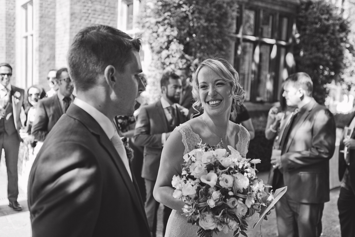 A bride smiling at her groom at a garden wedding