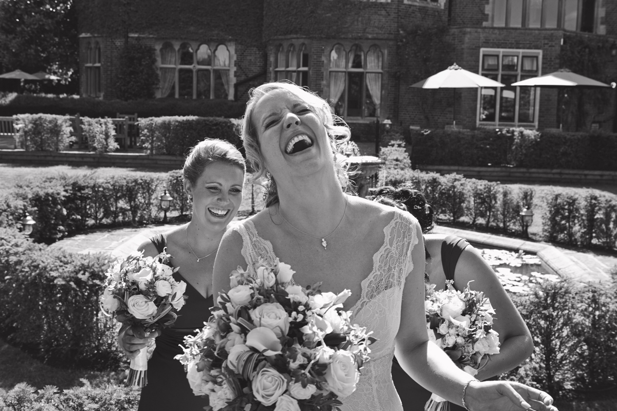 A bride laughing as her bridesmaids adjust her dress behind her