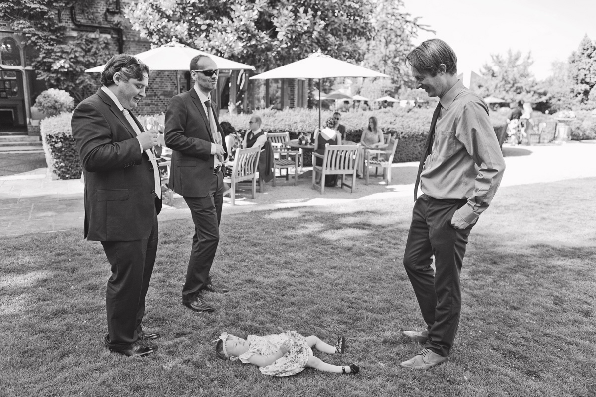 Three male wedding guests chatting at a garden reception with a small girl lying on the grass between them