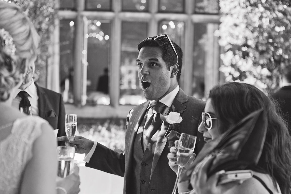 A black & white shot of a wedding guest gasping in surprise at a champagne reception