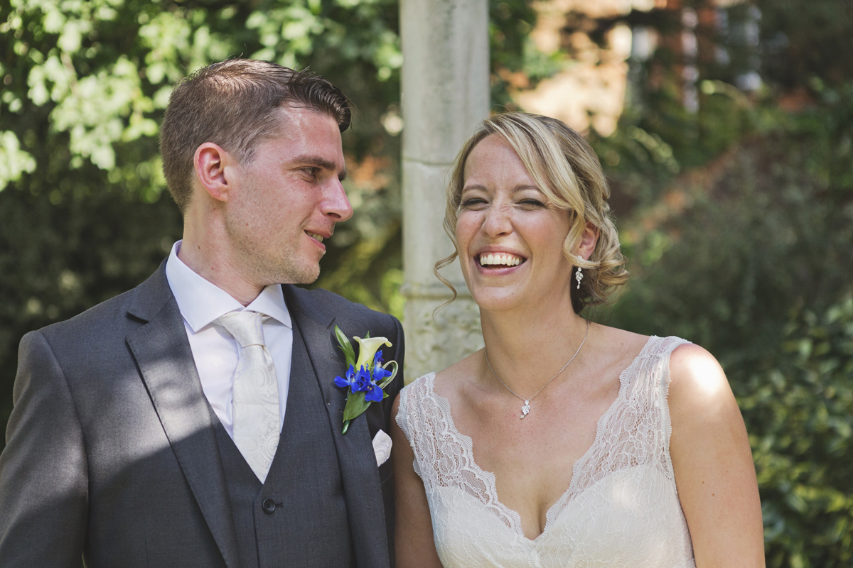 A bride laughing at her groom's joke at their wedding