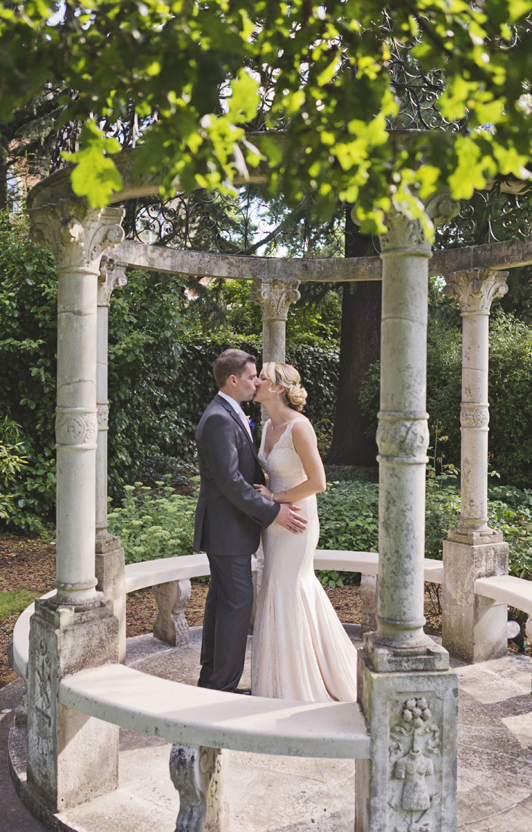 A bride and groom kissing under a stone gazebo on their wedding day