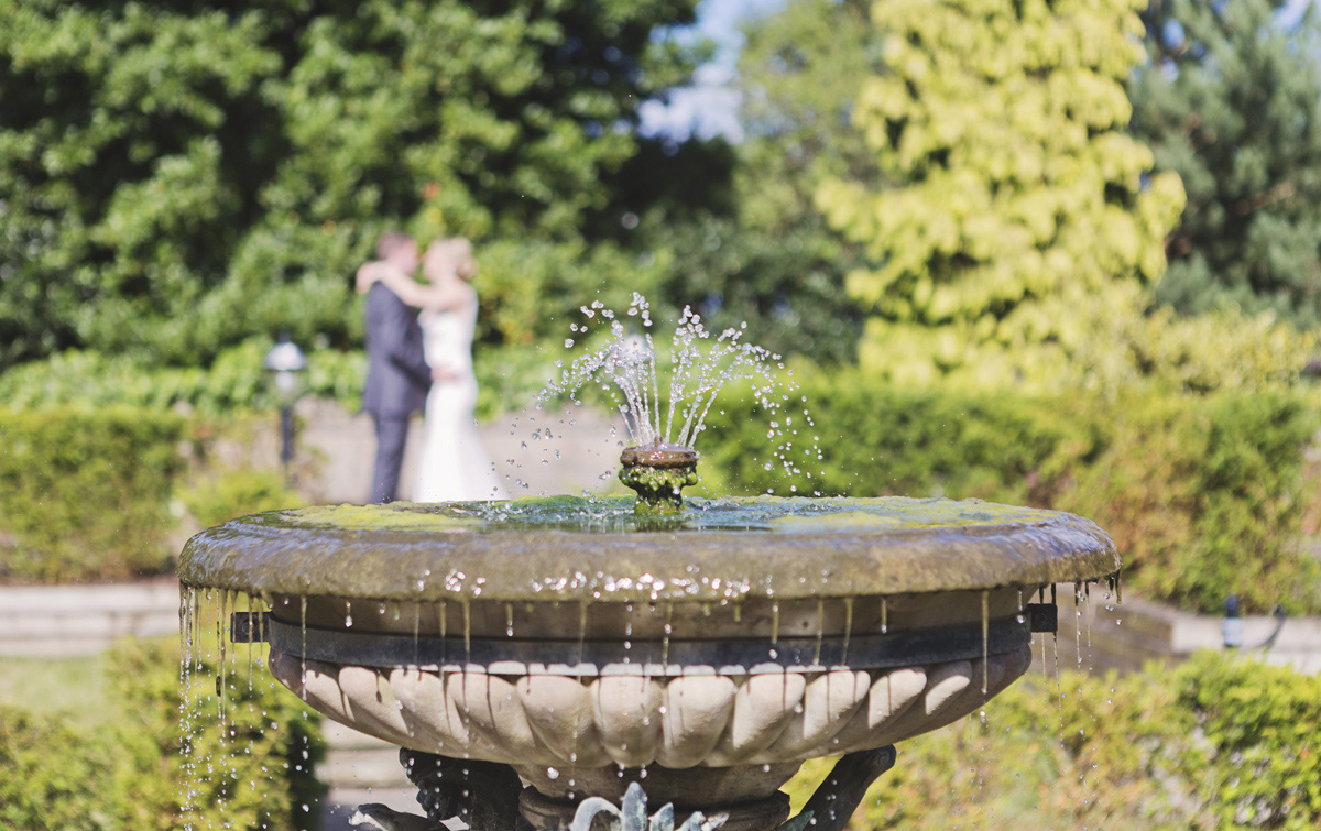 A water fountain with a blurred bride and groom hugging in the background