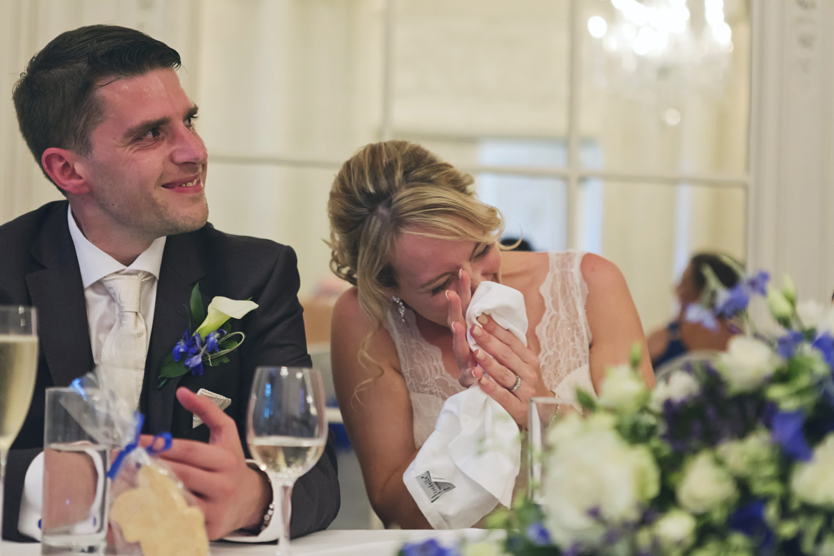 A bride & groom laughing during the speeches at their wedding