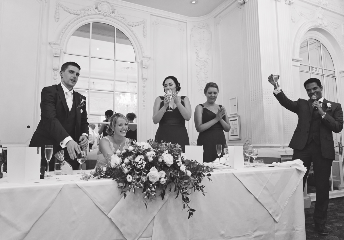 A groomsman toasts the bride and groom along with their bridesmaids at a wedding